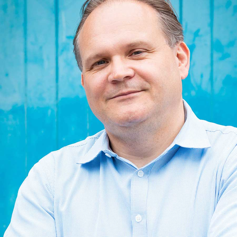 Man in shirt in front of bright blue background