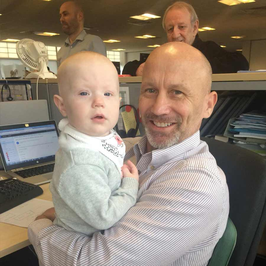 A male client holding a baby in an office environment