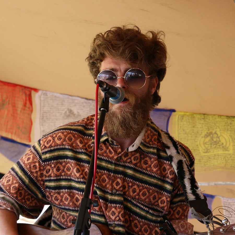 Male acoustic artist performing at a festival